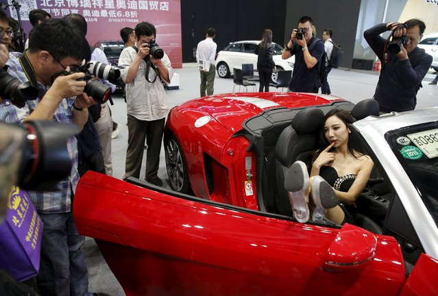 Visitors take pictures of a promotional model posing in an Audi R8 Spyder during the Imported Auto Expo in Beijing, China, September 24, 2015. (Photo by Kim Kyung-Hoon/Reuters)