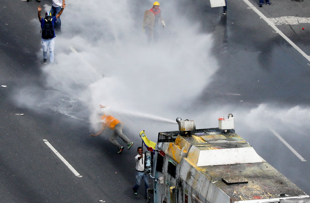 """Opposition lawmaker Carlos Paparoni is hit by jets of water during riots at a march to the state ombudsman's office in Caracas, Venezuela, May 29, 2017. A group of young Venezuelan lawmakers has risen to prominence on the violent front line of anti-government marches that have shaken the South American country for three months, bringing 75 deaths. On the streets daily leading demonstrators, pushing at security barricades and sometimes picking up teargas canisters to hurl back at police and soldiers, the energetic National Assembly members are heroes to many opposition supporters. Carlos Garcia Rawlins: """"I remember clearly how instants after I spotted Paparoni standing in front of """"The Whale"""", the common name of the water cannon armoured cars, he was flying through the air due to the unstoppable power of the water, as if he was a feather. Fellow protesters had to drag him out of the place, because from where I was, he seemed to have been unconscious"""". (Photo by Carlos Garcia Rawlins/Reuters)"""