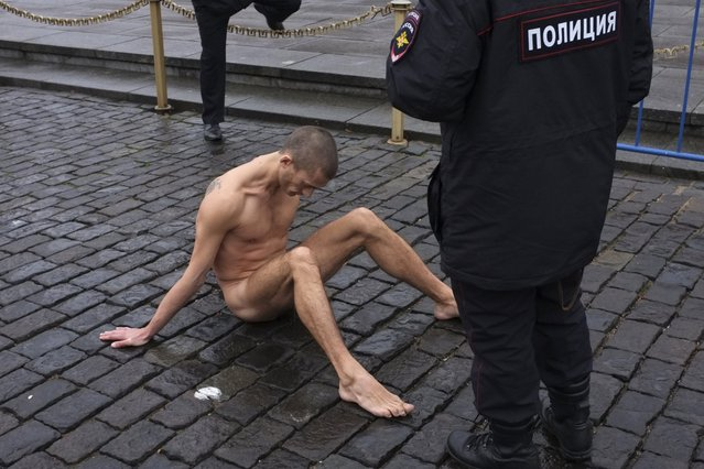 Artist Pyotr Pavlensky sits on the pavestones of Red Square during a protest action in front of the Kremlin wall in central Moscow November 10, 2013. (Photo by Maxim Zmeyev/Reuters)