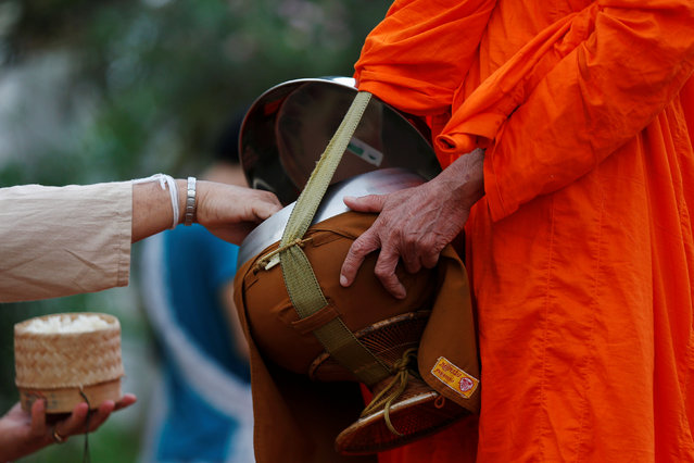 A Buddhist monk receives rice while collecting alms early morning in Luang Prabang, Laos July 31, 2016. (Photo by Jorge Silva/Reuters)