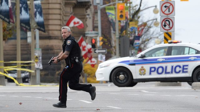 An Ottawa police officer runs with his weapon drawn outside Parliament Hill in Ottawa on Wednesday October 22, 2014. (Photo by Sean Kilpatrick/AP Photo/The Canadian Press)
