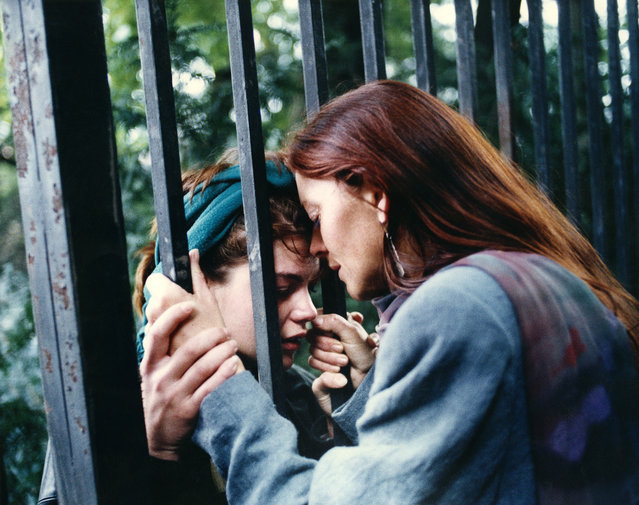 An East German mother cries as she says goodbye to her daughter as the fence of the West German embassy in Prague separates them Saturday, September 30, 1989.  The mother went back to East Germany and the daughter stayed with some 3,300 refugees who hope for emigration to the West. (Photo by Diether Endlicher/AP Photo)