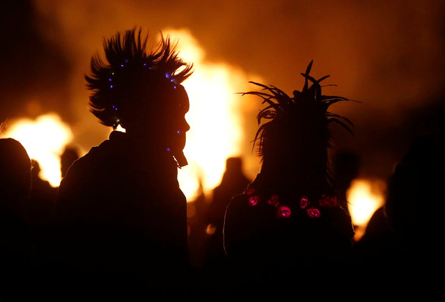 Participants watch the Temple Project burn as approximately 70,000 people from all over the world gathered for the 30th annual Burning Man arts and music festival in the Black Rock Desert of Nevada, U.S. September 4, 2016. (Photo by Jim Urquhart/Reuters)