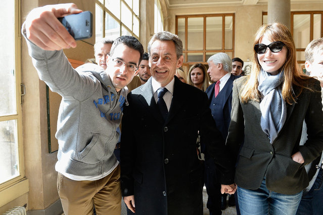 A man takes a selfie of Former French President Nicolas Sarkozy and Carla Bruni-Sarkozy (R) after they have voted on March 23, 2014 in Paris, France. (Photo by Pascal Le Segretain/Getty Images)