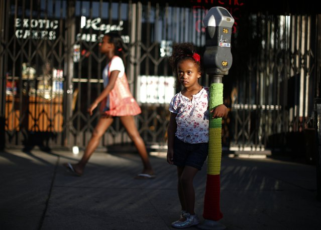 Mahlet Mogas, 5, stands with an arm around a parking meter decorated with wool in the colours of the Ethiopian flag in the Little Ethiopia area of Los Angeles, California September 14, 2014. (Photo by Lucy Nicholson/Reuters)