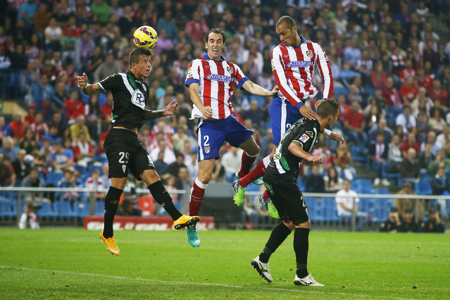 Atletico's Diego Gofin, top center, and Joao Miranda, top right, in action with Cordoba's Pinillos, left, during a Spanish La Liga soccer match between Atletico Madrid and Cordoba at the Vicente Calderon stadium in Madrid, Spain, Saturday, November 1, 2014. (Photo by Andres Kudacki/AP Photo)