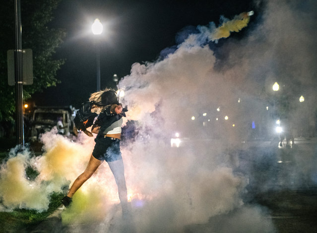 A demonstrator throws back a can of Tear gas on August 25, 2020 in Kenosha, Wisconsin. As the city declared a state of emergency curfew, a third night of civil unrest occurred after the shooting of Jacob Blake, 29, on August 23. Video shot of the incident appears to show Blake shot multiple times in the back by Wisconsin police officers while attempting to enter the drivers side of a vehicle. The 29-year-old Blake was undergoing surgery for a severed spinal cord, shattered vertebrae and severe damage to organs, according to the family attorneys in published accounts. (Photo by Brandon Bell/Getty Images)