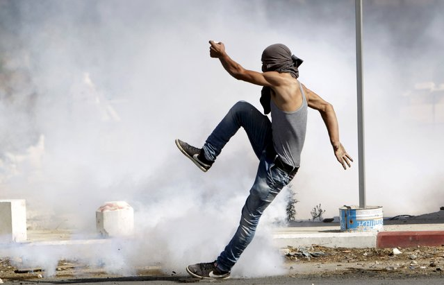 A Palestinian protester kicks a tear gas canister fired by Israeli troops during clashes in the West Bank city of Jenin October 9, 2015. (Photo by Mohammed Ballas/Reuters)