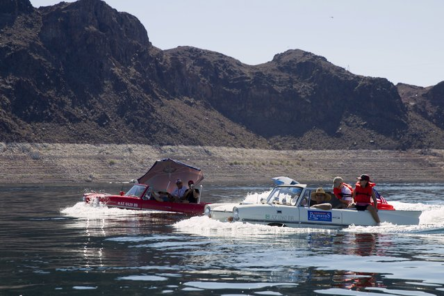 A 1963 Amphicar (L) driven by Rob Vondracek of Fountain Hills, Arizona, and a 1965 Amphicar driven by Dean Baker of Lake Havasu, Arizona head to Hoover Dam during the first Las Vegas Amphicar Swim-in at Lake Mead near Las Vegas, Nevada October 9, 2015. (Photo by Steve Marcus/Reuters)