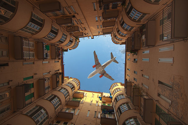 This photo taken in Naples, Italy is of a plane flying over a building with the photo taken at the perfect time while the plane is passing over an open area of the building, creating the Perfect Shot. The photo is actually not one single photo, but two photos combined together. One image is of the top part of the building and the plane flying over. A second image had to be combined for the lower portion of the building since the original photo's lighting of the bottom portion was bad quality, so two images were superimposed together. (Photo by Iryna)
