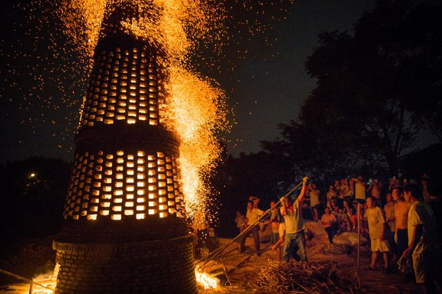 People burn a brick tower to celebrate the mid-autumn festival in Guangzhou, Guangdong province, China, September 14, 2016. (Photo by Reuters/Stringer)