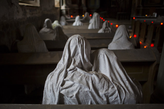 Ghost statues by artist Jakub Hadrava are placed at the St. George's church near Plzen on November 16, 2014 in Lukova, Czech Republic. Artist Jakub Hadrava created 32 plaster life-size ghost statues, which symbolize Sudeten Germans who lived in the village. St. George's church, which was build in the north-western Bohemian region of the Czech Republic in 1352, fell into disrepair after the roof collapsed during a funeral service in 1968. (Photo by Matej Divizna/Getty Images)