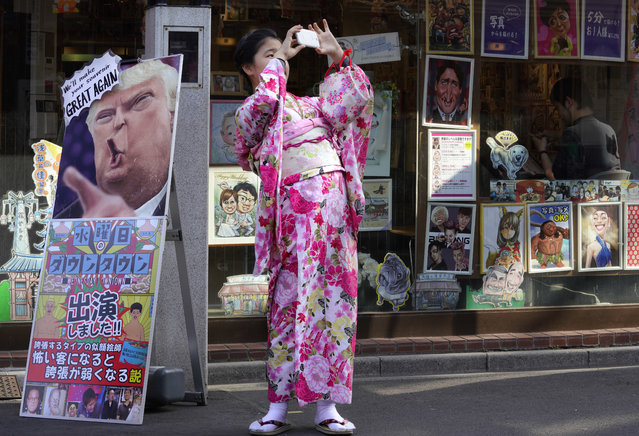 A tourist clad in Japanese kimono takes a picture in front of s portrait shop in Tokyo's Asakusa district, Thursday, February 15, 2018. Asakusa is a popular district four tourists in the capital. (Photo by Shizuo Kambayashi/AP Photo)