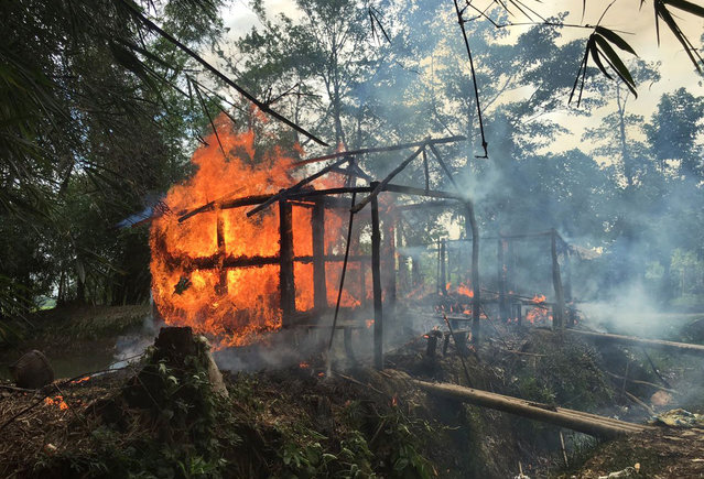 In this September 7, 2017, file photo, houses are on fire in Gawdu Zara village, northern Rakhine state, Myanmar. Two soldiers who defected from Myanmar's army and confessed on video to taking part in massacres, rape, and other crimes against the Muslim Rohingya minority are believed to be in the custody of the International Criminal Court in the Netherlands and should be prosecuted to obtain their evidence, a human rights organization said Tuesday. (Photo by AP Photo/File)
