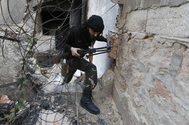 A fighter from the Al-Mujahideen army, which operates under the Free Syrian Army, walks through a hole in the wall on the Zeno street frontline in Aleppo November 18, 2014. (Photo by Hosam Katan/Reuters)