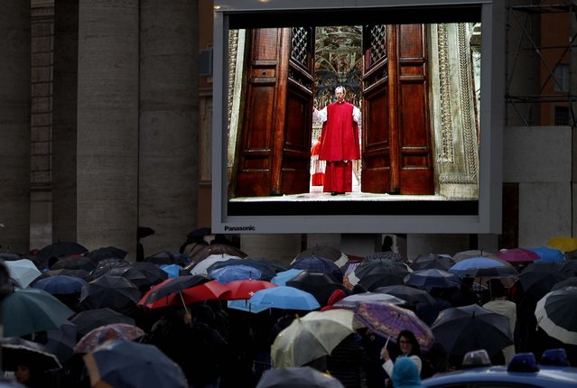 """People watch on a video monitor in St. Peter's Square as Monsignor Guido Marini, master of liturgical ceremonies, closes the double doors to the Sistine Chapel in Vatican City at the start of the conclave of cardinals to elect the next pope, on March 12, 2013. Marini closed the doors after shouting """"Extra omnes"""", Latin for """"all out"""", telling everyone but those taking part in the conclave to leave the frescoed hall. He then locked it. (Photo by Michael Sohn/Associated Press)"""