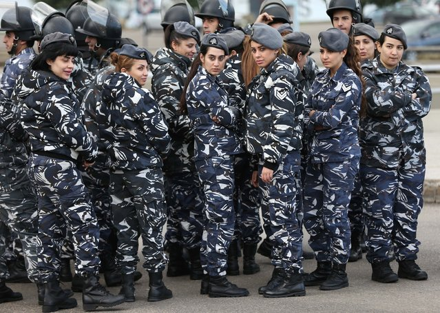 Lebanese policewomen stand behind riots police during a demonstration for the families of Lebanese soldiers who kidnapped by Islamic militants, a day after the Nusra Front threatened to kill one of the soldiers, and demanding that the government negotiate seriously with the militants, in downtown Beirut, Lebanon, Friday, November 28, 2014. Police have used water cannons to break up a protest by relatives of Lebanese soldiers held hostage by Islamic militants, during which they closed off a main highway in the capital. (Photo by Hussein Malla/AP Photo)