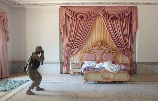 US Army Sergeant Craig Zentkovich from Connecticut belonging to the 1st Brigade Combat Team photographs a pink bedroom at Saddam Hussein's presidential palace, on April 13, 2003. (Photo by Romeo Gacad/AFP Photo/The Atlantic)