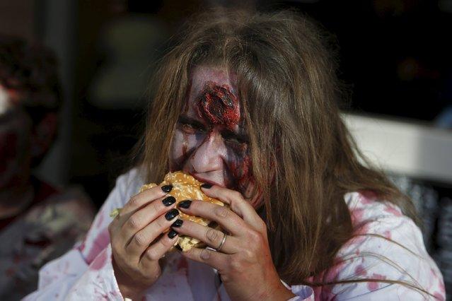 A participant in costume eats a hamburger inside a fast food restaurant after a Halloween parade in Kawasaki, south of Tokyo, October 25, 2015. (Photo by Yuya Shino/Reuters)