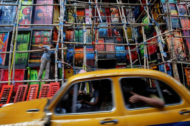 A taxi drives by as an Indian artist paints a makeshift pandal made with wood, fiber, metal, bamboo and colored paper by painter Rintu Das ahead of the Durga Puja festival in Calcutta eastern India, 29 September 2016.  Bengalis all over the world will be marking the festival representing the victory of good over evil and the celebration of female power from 08 to 11 October. (Photo by Piyal Adhikary/EPA)