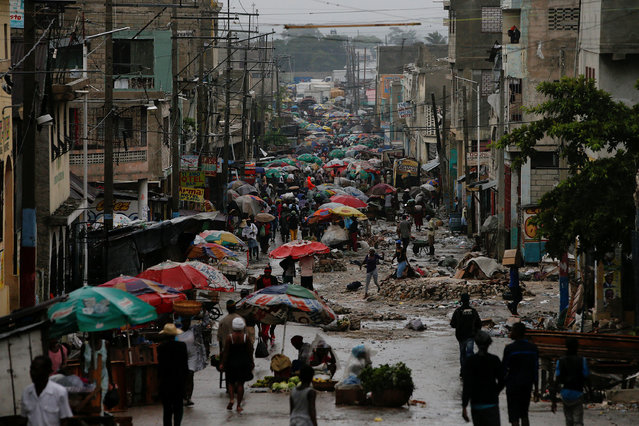 Vendors sell their goods on the street while Hurricane Matthew approaches in Port-au-Prince, Haiti October 3, 2016. (Photo by Carlos Garcia Rawlins/Reuters)