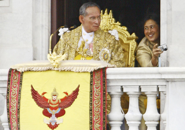 In this June 9, 2006, file photo, then Thailand's King Bhumibol Adulyadej, left, waits to address the crowd as Princess Sirindhorn takes photographs in Bangkok. Thais marked one year on Friday, October 13, 2017, since the death of King Bhumibol with formal ceremonies and acts of personal devotion before an elaborate five-day funeral later this month. (Photo by Wasan Wanichakorn/AP Photo)