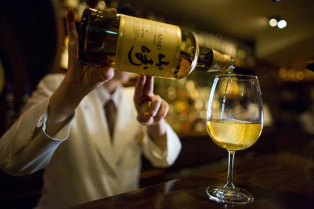 A bartender pours Yamazaki whisky at the Hibiya whisky bar in the Ginza district in Tokyo December 2, 2014. (Photo by Thomas Peter/Reuters)