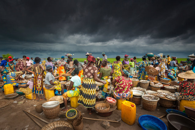 "Benin, west Africa. ""In the tiny country, large freshwater lakes provide a bountiful harvest for fishermen and open-air markets. This marketplace presents a colourful foreground as a storm builds on the horizon. Moments later, the skies opened in a tremendous downpour, prompting a frenzied search for shelter"". (Photo by Art Wolfe/The Guardian)"