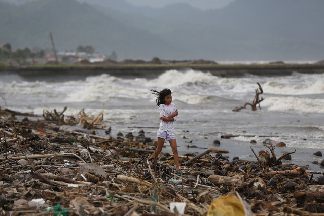 A girl walks along the shore as strong waves from Typhoon Hagupit hit Atimonan, Quezon province, eastern Philippines on Saturday, December 6, 2014. Haunted by Typhoon Haiyan's massive devastation last year, more than 600,000 people fled Philippine villages and the military went on full alert Saturday to brace for a powerful storm only hours away from the country's eastern coast. (Photo by Aaron Favila/AP Photo)