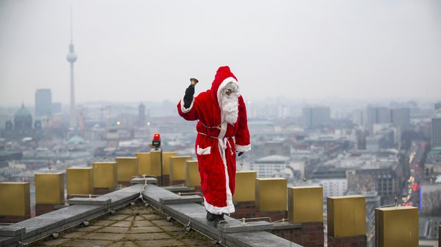 A man dressed as a Santa Claus poses on the roof of the Kollhoff Tower at Potsdamer Platz square in Berlin, December 14, 2014. (Photo by Hannibal Hanschke/Reuters)