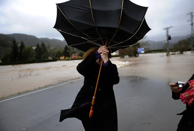 A woman attempts to hold onto her umbrella at a road partially submerged from floodwaters in Quinzanas, near Oviedo, Northern Spain January 19, 2013. (Photo by Eloy Alonso/Reuters)