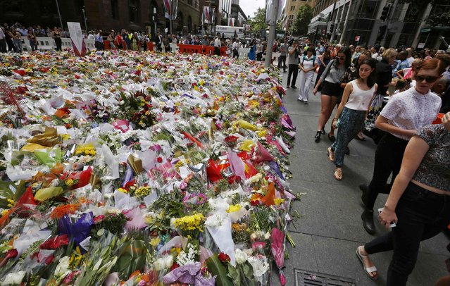 Members of the public observe the thousands of floral tributes left near the site of the Sydney cafe siege in Martin Place December 17, 2014. Tough new national security laws failed to prevent a deadly hostage crisis in the heart of Sydney this week, Australian Prime Minister Tony Abbott said on Wednesday, raising questions about the usefulness of such measures. (Photo by Jason Reed/Reuters)