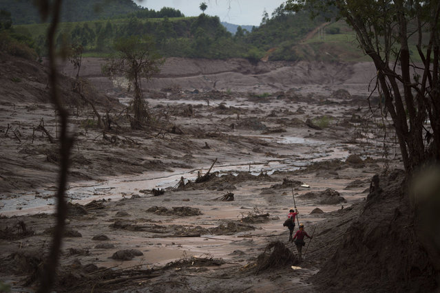 Rescue workers search for victims at the site where the town of Bento Rodrigues stood, after two dams burst on Thursday, in Minas Gerais state, Brazil, Sunday, November 8, 2015. Brazilian rescuers are looking for people still listed as missing following the burst of two dams at an iron ore mine which sent viscous red mud, water and debris flooding into the town, flattening all but a handful of buildings and killing dozens. (Photo by Felipe Dana/AP Photo)
