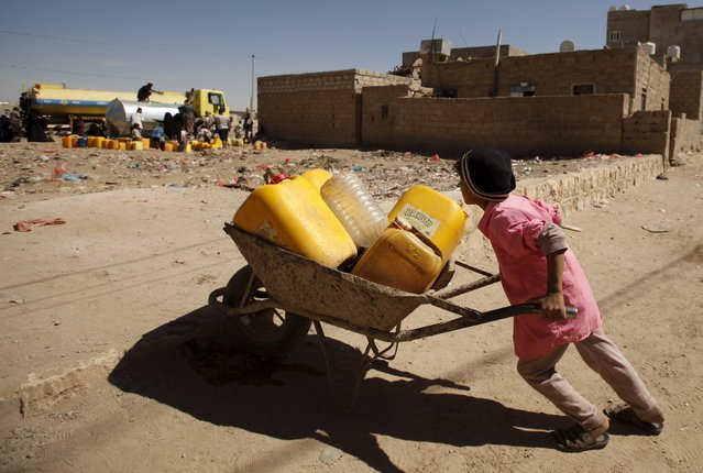 A boy pushes a wheel cart with plastic jerrycans to collect water from a tap in his neighbourhood amidst an acute shortage of water supplies in Yemen's capital Sanaa November 9, 2015. (Photo by Khaled Abdullah/Reuters)