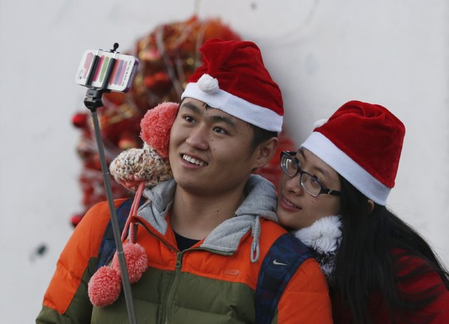 """A couple wearing Santa hats take a """"selfie"""" at a Catholic church in Beijing December 24, 2014. (Photo by Kim Kyung-Hoon/Reuters)"""