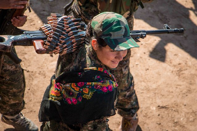 A Kurdish female fighter from the People's Protection Units (YPG) carries her weapon near al-Hawl area where fighting between Islamic State fighters and fighters from Democratic Forces of Syria are taking place in south-eastern city of Hasaka, Syria November 10, 2015. (Photo by Rodi Said/Reuters)