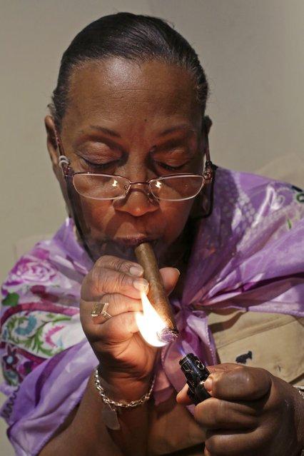Staff member Maria Regla, 60, smokes a hand-rolled cigar at a hotel in Havana December 19, 2014. (Photo by Enrique De La Osa/Reuters)