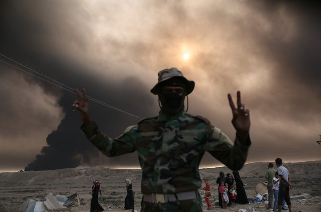 A Iraqi soldier looks on as smoke billows from the Qayyarah area, some 60 kilometres (35 miles) south of Mosul, on October 19, 2016, during an operation against Islamic State (IS) group jihadists to retake the main hub city. (Photo by Yasin Akgul/AFP Photo)