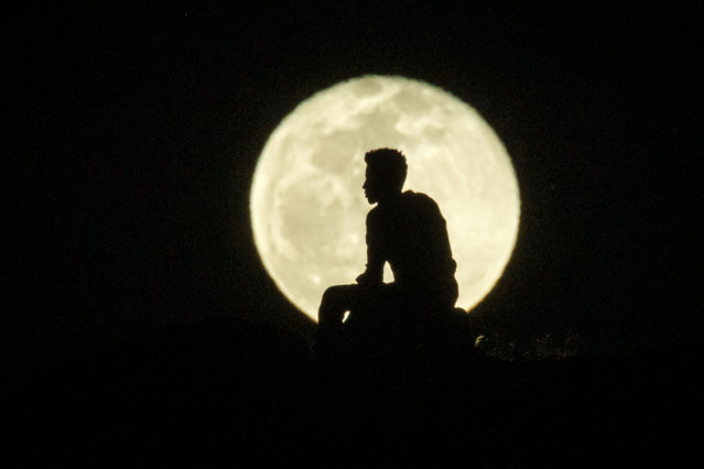 An Ehiopian man, who fled the Ethiopia's Tigray conflict as a refugee, watches the rising Moon on top of a hill at Um Raquba refugee camp in Gedaref, eastern Sudan, on December 1, 2020. More than 45,000 people have escaped from northern Ethiopia since November 4, after Prime Minister Abiy Ahmed ordered military operations against leaders of Tigray's ruling party in response to its alleged attacks on federal army camps. (Photo by Yasuyoshi Chiba/AFP Photo)
