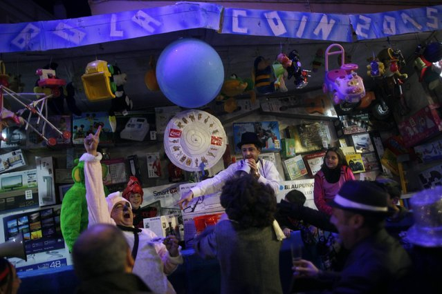 Revellers perform in a mock raffle as they take part in New Year's celebrations in Coin, near Malaga, southern Spain, early January 1, 2015. (Photo by Jon Nazca/Reuters)