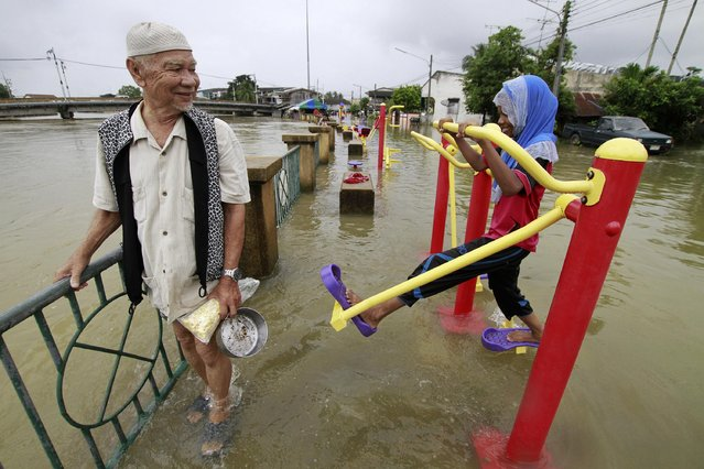 A man wades through a flooded street as a girl uses an exercise machine in the Pattani province December 29, 2014. Many parts of Thailand's southern provinces remain flooded and more heavy rains and strong winds were expected until the New Year, local media reported. (Photo by Surapan Boonthanom/Reuters)