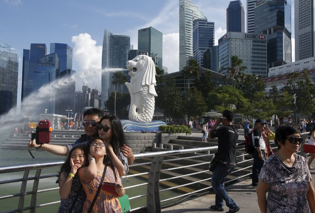 Tourists take photos by the famous Merlion fountain in Singapore July 29, 2015. (Photo by Edgar Su/Reuters)