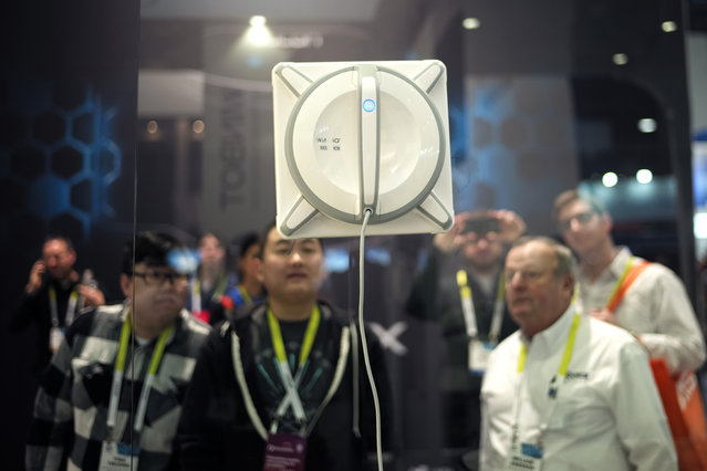 Attendees watch a Winbot, a window cleaning robot, clean the window at the Ecovacs Robotics booth at the International CES, Tuesday, January 6, 2015, in Las Vegas. (Photo by Jae C. Hong/AP Photo)
