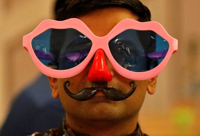 A man wearing a pair of goggles and plastic nose and mustache looks on during a party to celebrate the arrival of the New Year inside a hotel, amidst the spread of the coronavirus disease (COVID-19) in Ahmedabad, India, December 31, 2020. (Photo by Amit Dave/Reuters)