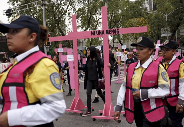 """Police officers surround people marching with pink crosses during the International Day for the Elimination of Violence Against Women, in Mexico City, November 25, 2015. The writing on the cross reads """"Not one (woman) less"""". (Photo by Daniel Becerril/Reuters)"""