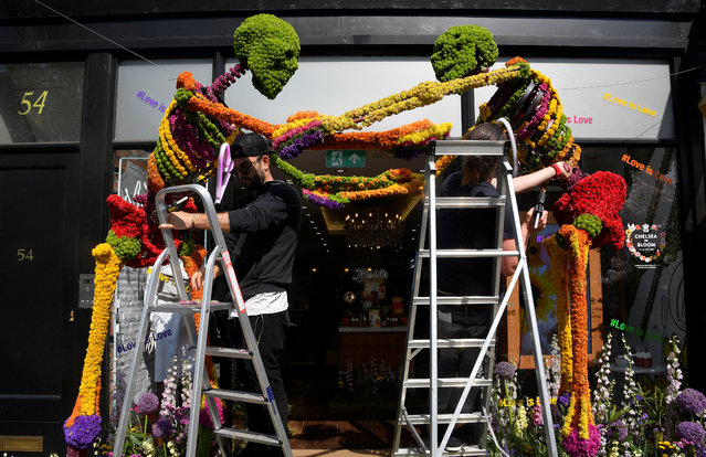 Florists work on a floral display and design outside of a shop front which is participating in the Chelsea In Bloom festival in London, Britain on May 22, 2018. (Photo by Toby Melville/Reuters)