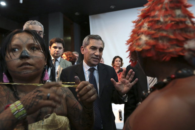 Minister of the General Secretariat of the Presidency of Brazil Gilberto Carvalho speaks with Munduruku Indians during a meeting at the Planalto Palace to try to resolve the occupation of the construction of Belo Monte, in Brasilia June 4, 2013. President Dilma Rousseff's government sought on Tuesday to defuse mounting conflicts with indigenous groups over its decision to stop setting aside farm land for Indians and plans to build more hydroelectric dams in the Amazon. (Photo by Ueslei Marcelino/Reuters)