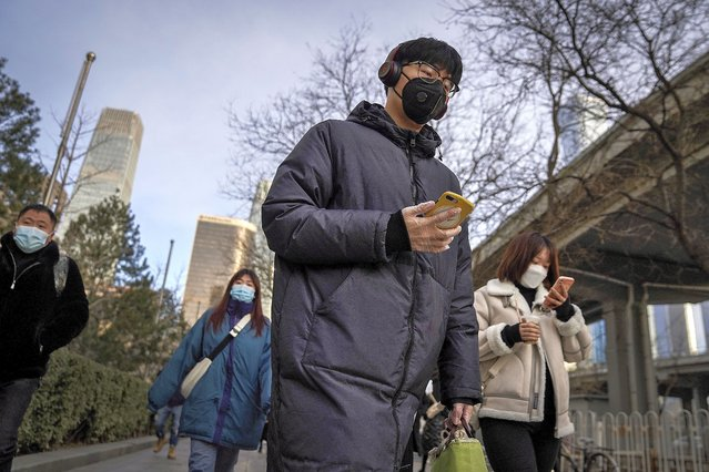 A man wearing a face mask and a disposable gloves to help curb the spread of the coronavirus heads to work with other masked people during the morning rush hour in Beijing, Monday, January 11, 2012. Chinese health authorities say scores more people have tested positive for coronavirus in Hebei province bordering on the capital Beijing. The outbreak focused on the Hebei cities of Shijiazhuang and Xingtai is one of China's most serious in recent months and comes amid measures to curb the further spread during next month's Lunar New Year holiday. (Photo by Andy Wong/AP Photo)