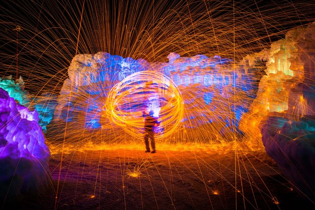 Scott Stringham creating a fire ball in the ice castle. (Photo by Sam Scholes/Caters News)