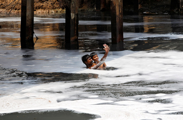 A man and a boy pose for a selfie while swimming in the polluted waters of the Yamuna River on World Environment Day in New Delhi, India, June 5, 2018. (Photo by Saumya Khandelwal/Reuters)
